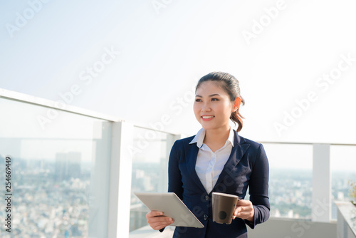 Attractive businesswoman drinking a coffee and using a digital tablet standing outdoor and looking the city - 254669449