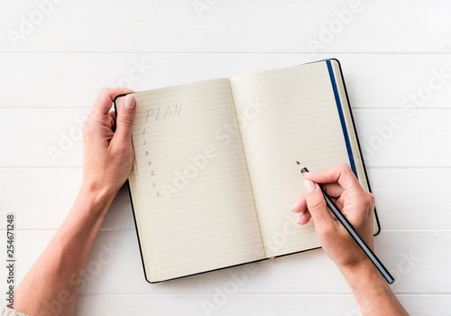 Foto Murales Top view of girl creating a plan in notebook on white table