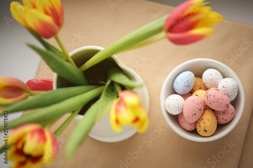Easter candy egg on with defocused tulips bouquet