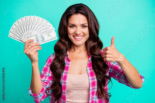 Close up photo beautiful she her lady hands arms hold fan bucks money look glad  amazed show thumb up buy buyer wear casual plaid checkered pink shirt outfit isolated teal bright vivid background
