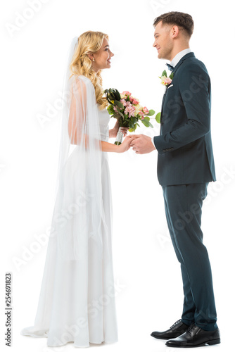 smiling bride in white wedding dress and happy groom in black suit holding hands and looking at each other isolated on white