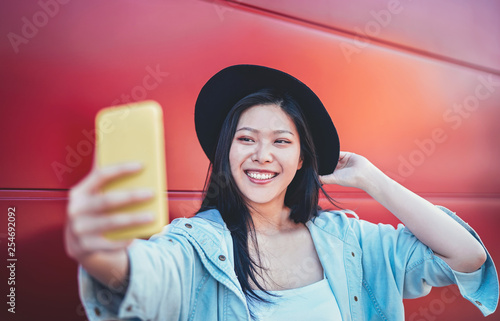 Happy Asian girl doing a video story with mobile smart phone outdoor - Chinese woman web influence having fun with new trends social networks app - People, millennial generation and technology concept