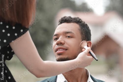 Leinwanddruck Bild makeup artist makes makeup young politician before a public speech