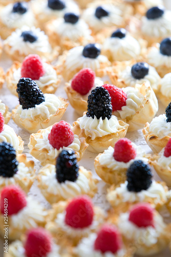 details of wedding treats with white cream and black berries and raspberries