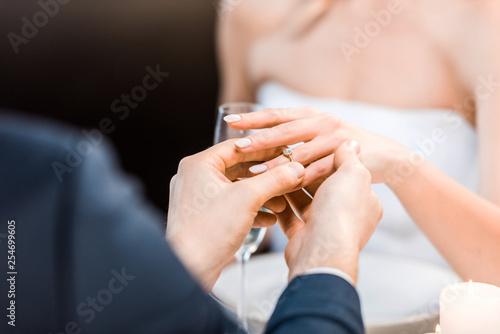 selective focus of man putting wedding ring on brides finger on black background