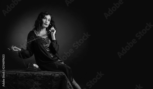 Portrait of attractive brunette  in negligee with old phone. - 254699633