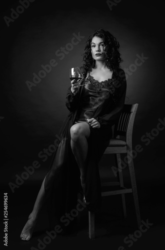 obraz PCV Portrait of attractive brunette with glass of brandy on a black background.