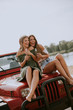 Leinwanddruck Bild - Attractive young women sitting on a convertible car by river