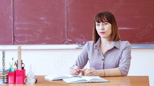portrait of the teacher at the table against the blackboard