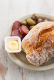 bread with butter, olives and smoked sausage on dish on wooden background
