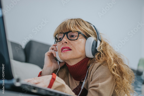 woman with laptop listening to music with headphones - 254719847