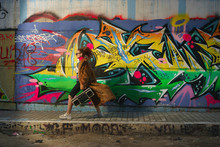 "Постер, картина, фотообои ""Photo of young hip hop girl walking against graffiti wall with boombox """