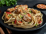 Asian noodles with chicken teriyaki , sesame, rustic stone background. Closeup. Chinese/Japanese noodles