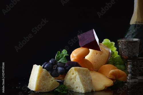 Still life on a black background with cheeses and a bottle of champagne. The concept of still life and vintage. © Alla