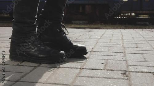 Men legs in boots walking on street sett