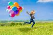 Leinwanddruck Bild - Glückliches Mädchen spring mit vielen bunten Luftballons über eine grüne Wiese