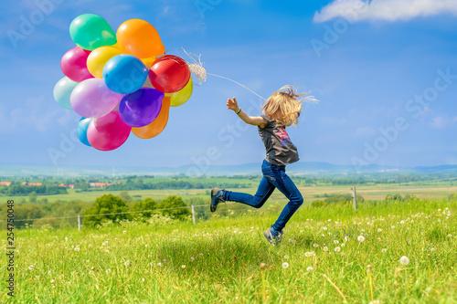Leinwanddruck Bild Glückliches Mädchen spring mit vielen bunten Luftballons über eine grüne Wiese
