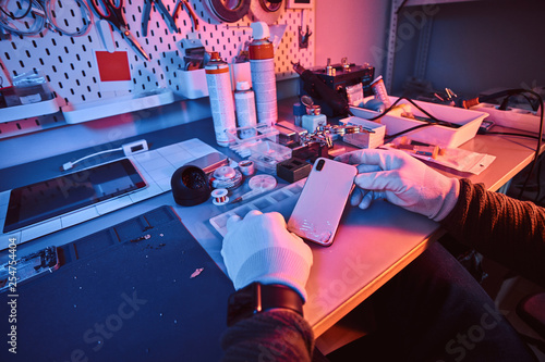 Foto Murales Electronic technician holds a modern smartphone with a broken body sitting at a table in a repair shop. Illumination with red and blue lights