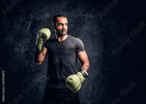 Leinwanddruck Bild Portrait of a brutal professional fighter in a black shirt and gloves posing for a camera. Studio photo against a dark textured wall