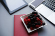 Leinwanddruck Bild - Raspberry and blackberries, healthy lunch in the office. Laptop, tablet, smartphone and notebook on a table