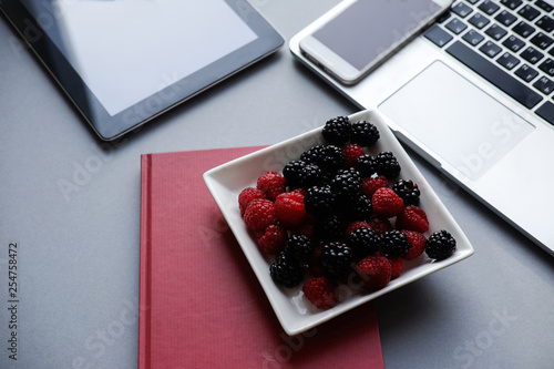 Leinwanddruck Bild Raspberry and blackberries, healthy lunch in the office. Laptop, tablet, smartphone and notebook on a table