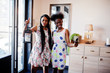 Two black african girlfriends at summer dresses posed in modern house with lantern and making selfie by phone.