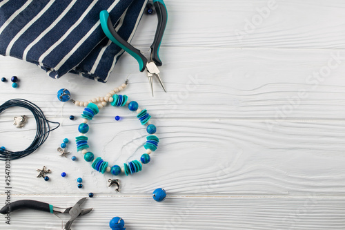 Handmade turquoise bracelet, overhead flat lay composition with pliers, beads and tools