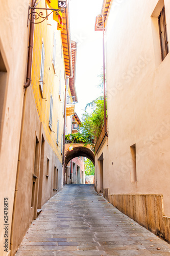 Chiusi, Italy narrow street alley with arch in small historic medieval town village in Umbria vertical view during day with orange yellow bright vibrant vivid color walls - 254786875