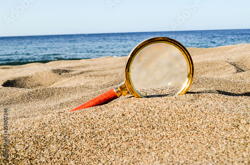 Magnify Glass on the Sand Beach - 254807246