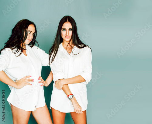 Leinwanddruck Bild two sisters twins girl posing, making photo selfie, dressed same white shirt, diverse hairstyle friends, lifestyle people concept