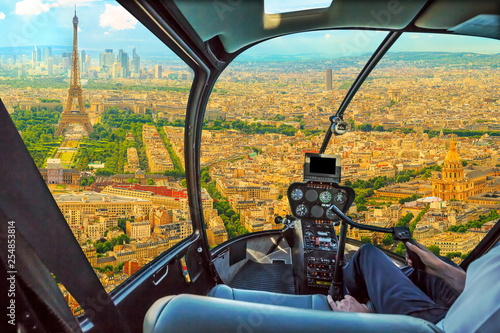 Helicopter cockpit flying on Panorama of Tour Eiffel and national residence of the Invalids in Paris, French capital, Europe. Scenic flight above Paris skyline and cityscape background.