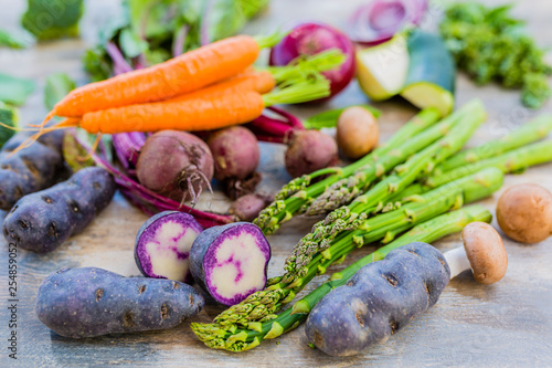 Raw and fresh spring vegetables on a wooden background. © iMarzi