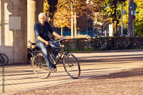 Leinwanddruck Bild Radfahrer Stadt Sonne