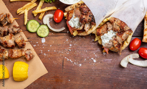 Gyro pita, shawarma, souvlaki. Two pita bread wraps and meat skewers on wooden table - 254869067