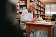 Leinwandbild Motiv Senior man writing sitting in a university classroom