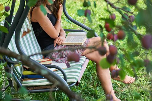 Teen girl reads a book sitting on a garden swing in the summer garden.