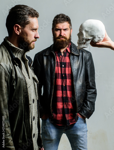 Looking deep into eyes of your fear. Man brutal bearded hipster looking at skull symbol of death. Overcome your fears. Be brave. Focused on breaking fear. Psychology concept. Human fears and courage
