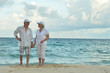 Leinwanddruck Bild - Portrait of elderly couple standing on tropical beach
