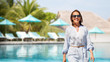 people and leisure concept - happy smiling woman walking over swimming pool of touristic resort background