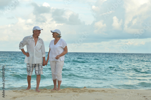 Leinwanddruck Bild Portrait of elderly couple standing on tropical beach