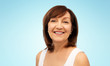 beauty and old people concept - portrait of smiling senior woman over blue background