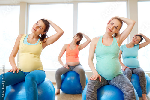 pregnancy, sport, fitness and healthy lifestyle concept - group of happy pregnant women training with exercise balls in gym - 254883075
