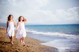 belle bambine a camminare sulla riva del mare