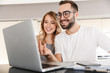 Amazing happy young loving couple sitting at the kitchen using laptop computer.