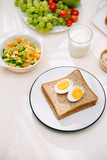 Healthy Breakfast served with milk, croissants, egg, cereals, oatmeal and fruits.