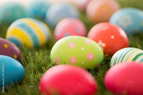 easter, holidays and tradition concept - colored eggs on artificial grass - 254886266