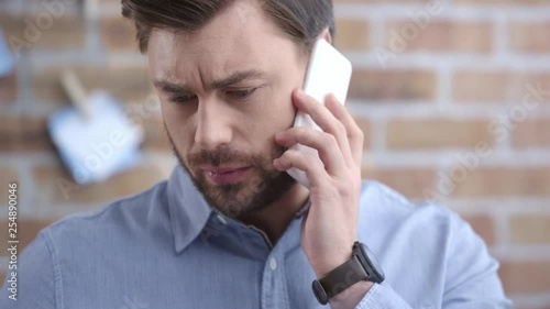 Businessman in blue shirt with wristwatch talking on smartphone and looking at document at workplace