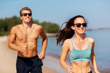 fitness, sport and technology concept - happy couple with earphones running along summer beach