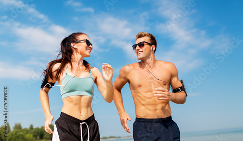 Leinwandbild Motiv fitness, sport and technology concept - happy couple with earphones and arm bands running along summer beach