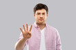 count and people concept - young man showing four fingers over grey background